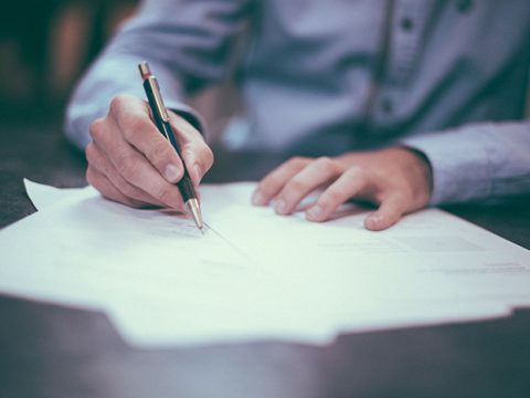 image of man writing on paper with a pen